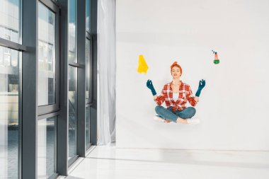 floating girl in jeans and plaid shirt meditating with rag and spray on white background