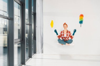 floating girl in jeans and plaid shirt meditating with rag and duster on white background