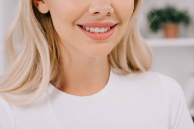 cropped view of blonde woman with toothy smile