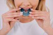 Fotografie Ausgeschnittene Ansicht einer Frau, die eine kieferorthopädische Zahnspange anzieht, isoliert auf weiß
