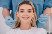 dentist holding mouth mirror and dental probe while young woman looking at camera
