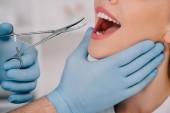 Ausgeschnittene Ansicht des Zahnarztes in Latexhandschuhen mit zahnärztlichem Instrument zur Untersuchung der Zähne einer Frau in der Klinik