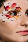 close up of attractive girl with floral petals around eye