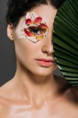 attractive girl with floral petals around eye holding leaf isolated on grey