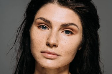 attractive brunette young woman with freckles on face isolated on grey