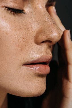 close up view of tender woman with freckles on face isolated on grey