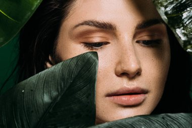 tender young woman with freckles posing with green leaves