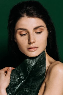 Portrait of beautiful woman with freckles on face posing with palm leaf isolated on green