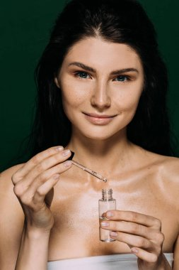 smiling attractive woman holding bottle with serum isolated on green