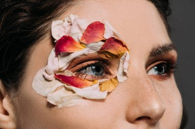 close up of beautiful woman with floral petals around eye isolated on grey