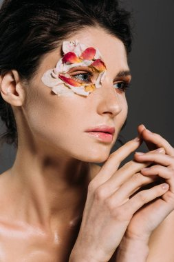 tender brunette girl with petals around eye isolated on grey