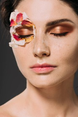 beautiful young woman with petals and makeup on closed eyes isolated on grey
