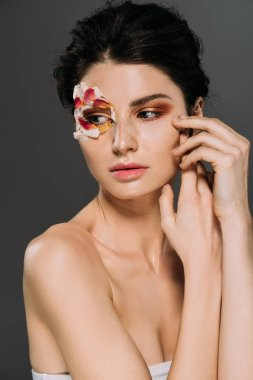 beautiful tender girl with floral petals around eye isolated on grey