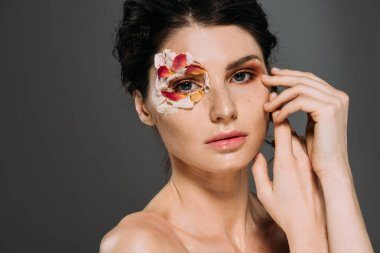 tender girl with floral petals around eye isolated on grey