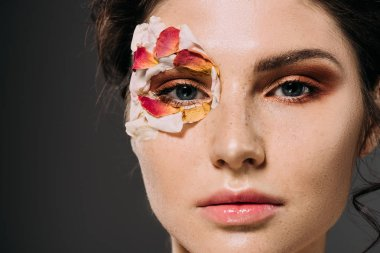 attractive young woman with makeup and floral petals around eye isolated on grey