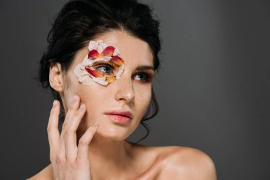 attractive tender girl with petals around eye isolated on grey