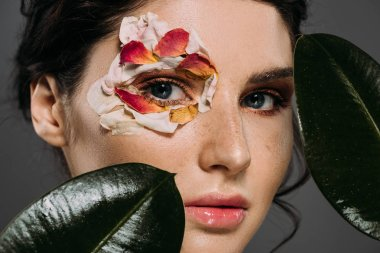 beautiful girl with floral petals around eye holding leaves isolated on grey