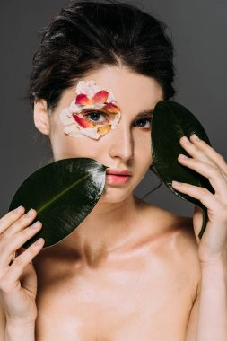 beautiful young woman with floral petals around eye holding leaves isolated on grey