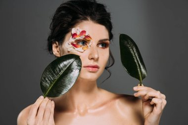 attractive woman with flower petals around eye holding leaves isolated on grey