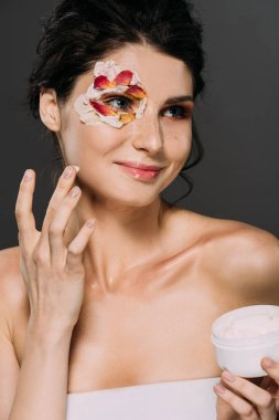 beautiful smiling woman with petals on face applying moisturizing cream isolated on grey
