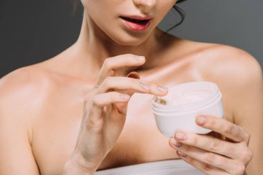 cropped view of woman holding plastic container with face cream isolated on grey