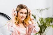 Okouzlující mladá žena poslech hudby do sluchátek a při pohledu na fotoaparát