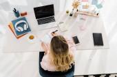 Szőke nő írásban notebook, a munkahelyen, felülnézet