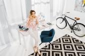 Bella bionda donna in pantaloni bianchi, bere il caffè a casa ufficio