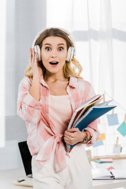 Amazed blonde woman in checkered shirt holding notebooks and listening music