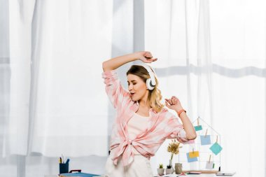 Charming young woman dancing and listening music at home
