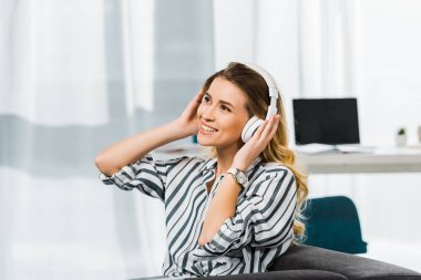 Happy woman in striped shirt sitting on sofa and listening music in headphones