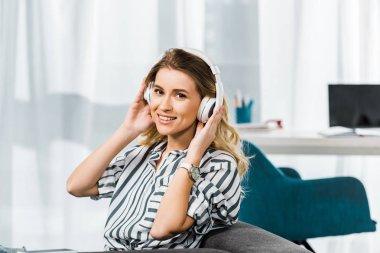 Happy blonde woman in striped shirt listening music in headphones stock vector