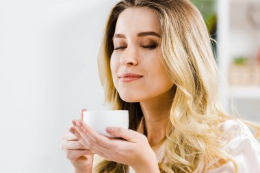 Relaxed young woman holding coffee cup with closed eyes