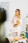 Zasněný mladá žena v pyžamu drží croissant a sklenice pomerančové šťávy