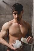 Fotografia uomo nudo bello che tiene luffa e doccia gel