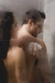 Fotografia messa a fuoco selettiva delluomo nudo e donna attraente che cattura acquazzone con luffa