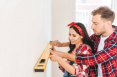 cheerful couple holding measuring level near wall at home