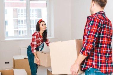 Happy woman holding box and looking at man at home stock vector
