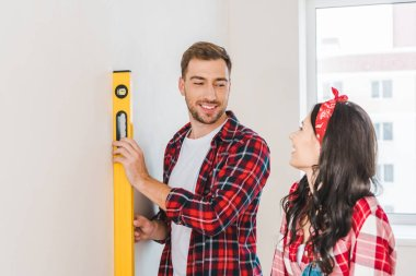 cheerful man holding measuring level near girlfriend at home