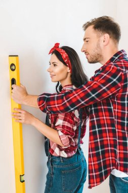 happy couple holding measuring level near wall at home