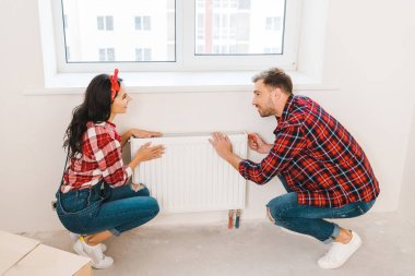 cheerful couple touching heating radiator while sitting near window at home