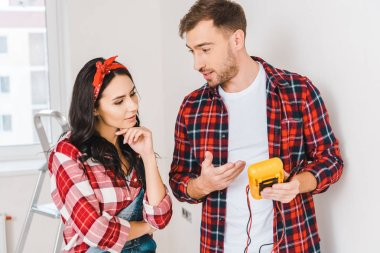 handsome man holding digital multimeter while standing near woman at home