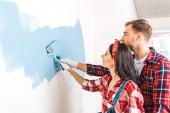 Fotografie fröhliche Mann und Frau malen Wand in blauer Farbe zu Hause