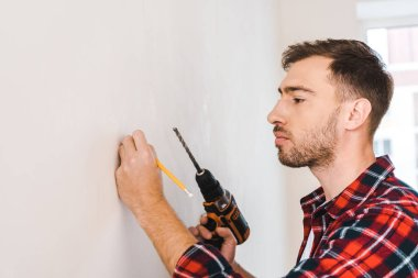 handsome man holding drilling machine and pencil in hands while standing near wall