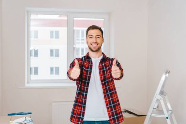 Happy man showing thumbs up while standing at home stock vector