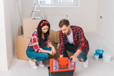 Man and woman sitting and looking at toolbox at home stock vector