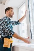 Veselá údržbář s pásem nástroj usmívající se při otevírání okna