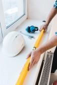 Fotografia ritagliate la vista del handyman holding misurazione livello vicino a oggetti
