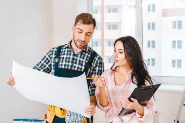 cheerful handyman holding blueprint near attractive client with clipboard and pencil