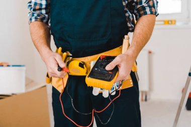 cropped view of handyman holding digital multimeter in hands